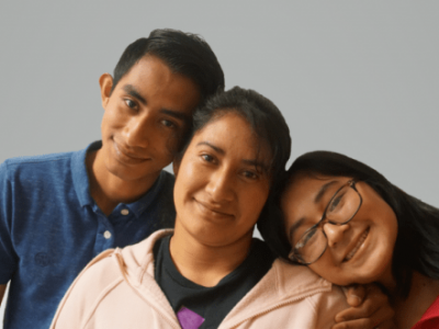 Three young people smile together.