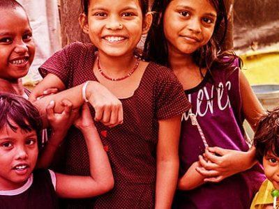Five children smile together.