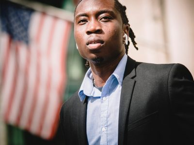 A young man stands next to an American flag.